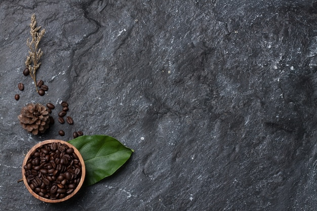 Mise à plat des grains de café dans une tasse en bois sur feuille verte, pin et fleur sèche sur la texture de fond de pierre noire