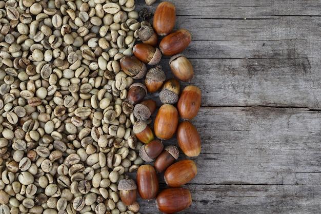 Mise à plat de grains de café torréfiés au milieu et gland sur bois en arrière-plan
