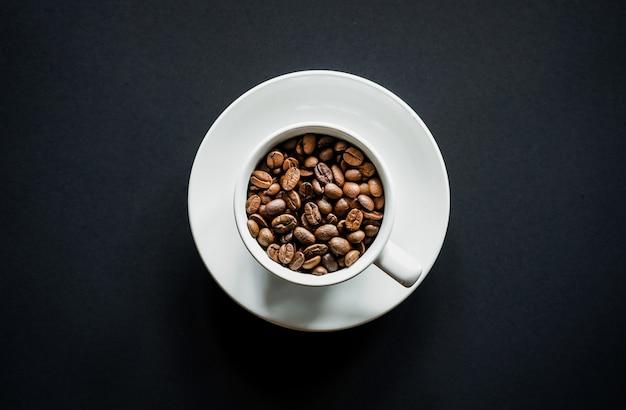 Mise à plat de grains de café torréfiés dans du café blanc sur fond noir avec espace de copie