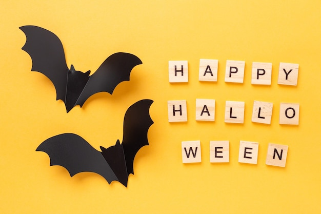 Mise à Plat D'halloween Avec Texte Happy Halloween Et Deux Chauves-souris Volantes Sur Fond Jaune - Image Photo Premium