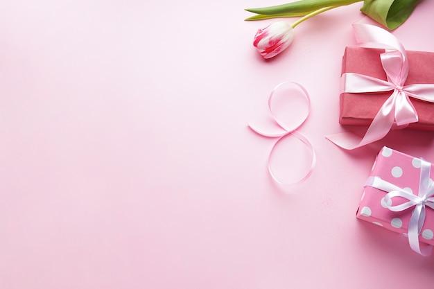 Mise à plat huit de ruban rose avec une belle tulipe et des cadeaux sur un fond rose. 8 mars, journée internationale de la femme.