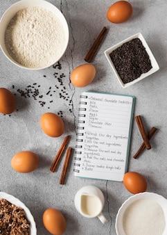 Mise à plat des ingrédients alimentaires avec cahier et mélange de desserts