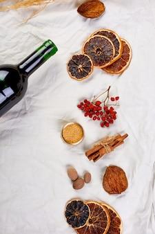 Mise à plat d'ingrédients et bouteille de vin rouge pour le vin chaud saisonnier d'hiver sur nappe en lin textile blanc, nature morte, fond de texture de tissu, boisson de noël, espace de copie.