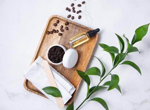 Mise à plat avec des ingrédients naturels pour le gommage au café du corps à la maison avec des grains de café et de l'huile d'olive sur du marbre