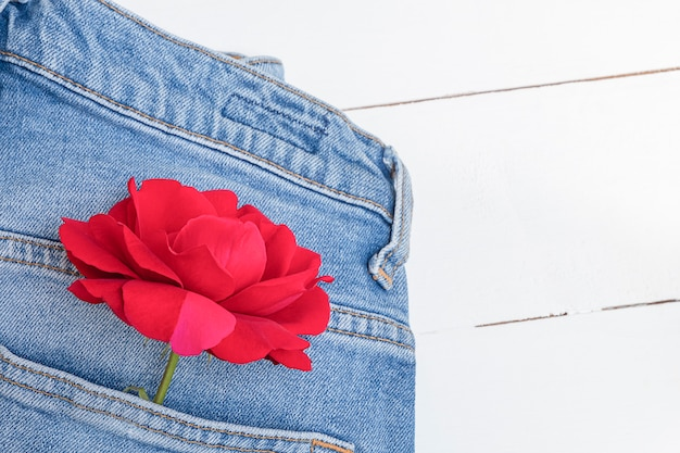 Mise à plat avec un jean bleu et une fleur rose rouge sur une table en bois blanche