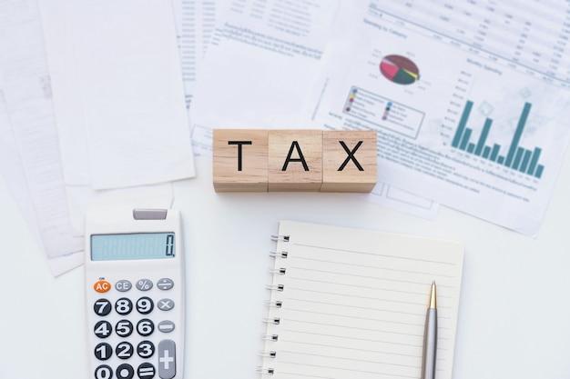 Mise à plat de la lettre d'impôt sur le cube en bois, ordinateur portable, calculatrice, factures sur un bureau blanc. affaires, finances, concept de planification fiscale