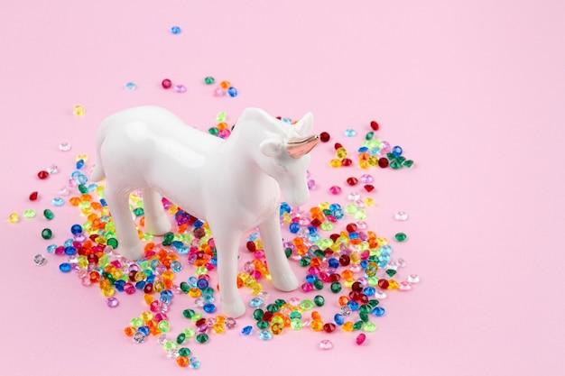 Mise à plat avec une licorne blanche et des paillettes colorées sur le mur rose. magique surréaliste, style de conte de fées. composition minimale