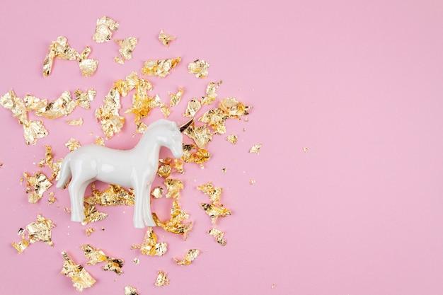 Mise à plat avec une licorne blanche et des paillettes dorées sur le mur rose. magique surréaliste, style de conte de fées. composition minimale, vue de dessus