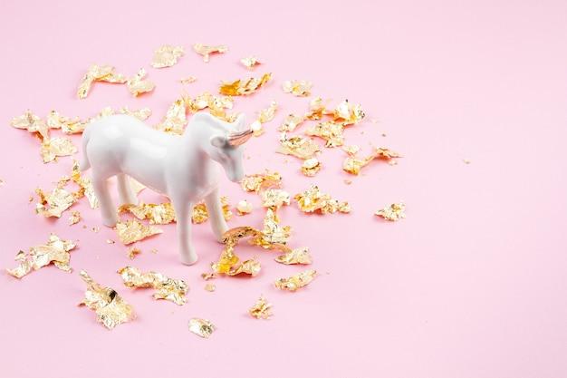 Mise à plat avec une licorne blanche et des paillettes dorées sur le mur rose. magique surréaliste, style de conte de fées. composition minimale