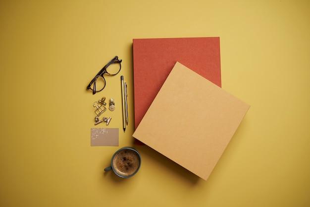 Mise à plat avec livres, tasse à café, lunettes de lecture, stylo et crayons sur jaune.
