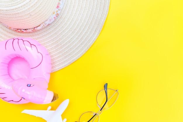 Mise à plat avec des lunettes de soleil d'avion, un chapeau et un flamant gonflable isolé sur fond jaune