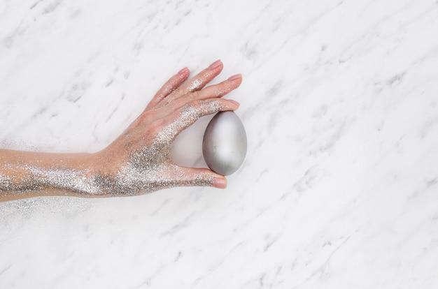 Mise à plat de la main couverte de paillettes tenant l'oeuf de pâques peint