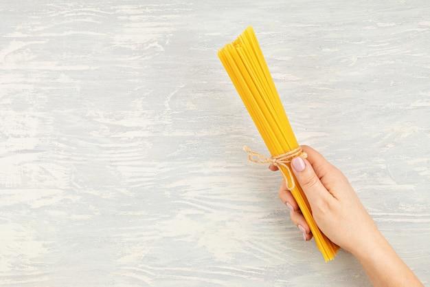 Mise à plat de la main de femme tenant des spaghettis pour la cuisson des pâtes italiennes. vue de dessus du concept de cuisine italienne traditionnelle