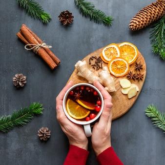 Mise à plat de la main masculine tenant une tasse de thé chaud au citron, canneberges, clous de girofle, anis, gingembre