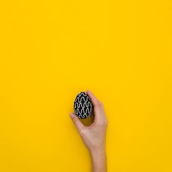 Mise à plat de la main tenant l'oeuf de pâques avec un design