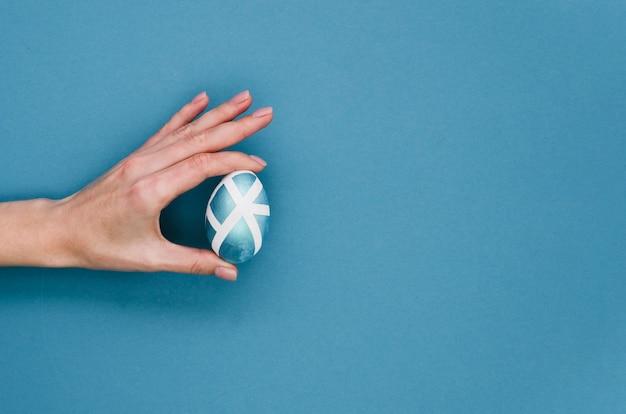 Mise à plat de la main tenant l'oeuf de pâques peint avec espace copie