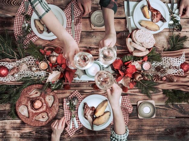 Mise à plat des mains d'amis manger et boire ensemble. vue de dessus des personnes ayant la fête, se rassemblant, célébrant ensemble à table rustique en bois