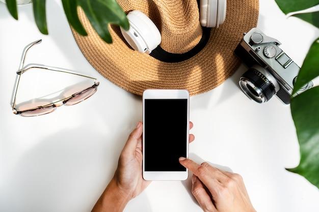 Mise à plat des mains de femme à l'aide de téléphone portable avec des articles d'été sur un bureau blanc.