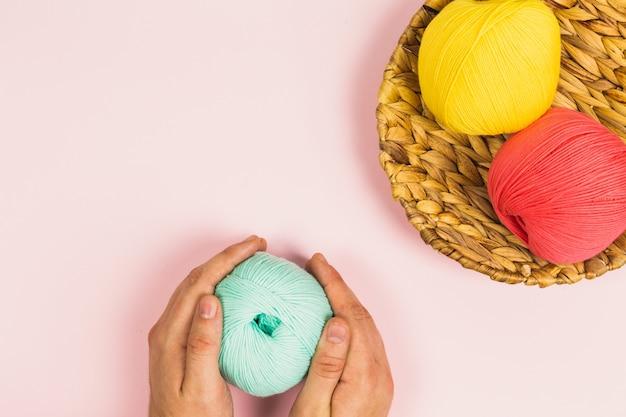 Mise à plat des mains de femme tenant une belle boule de menthe verte à côté de boules de corail rose et jaune foncé de coton dans un panier avec fond rose pastel et espace copie
