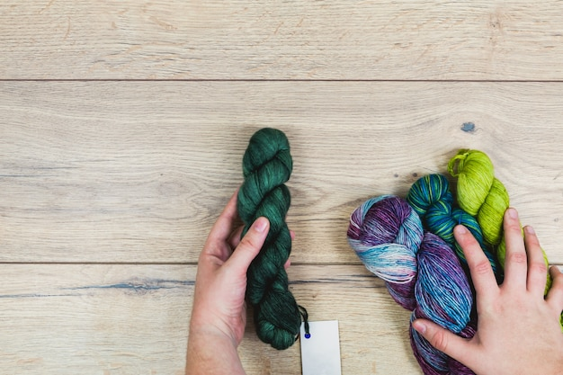 Mise à plat de mains humaines choisissant de belles échevettes dans des tons violets et verts avec étiquette vierge pour maquette sur une table en bois