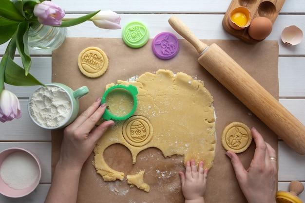 Mise à plat avec les mains de la mère et du bébé préparant les cookies à thème de pâques