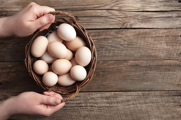 Mise à plat avec les mains tenant le panier avec des œufs de poule bio sur fond en bois. concept de ménage biologique avec des œufs de poules élevées en plein air et en pâturage
