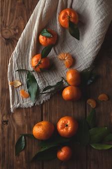 Mise à plat avec des mandarines avec des dépliants sur un fond en bois.