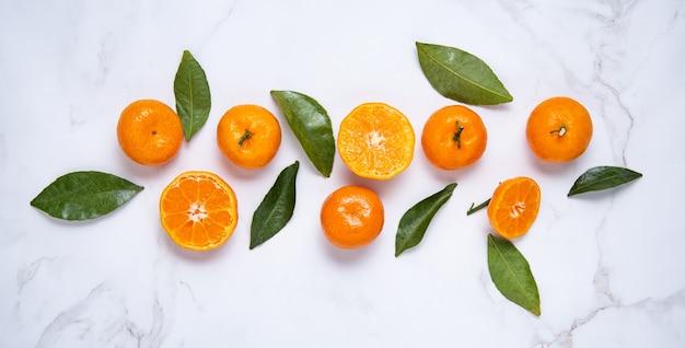 Mise à Plat Des Mandarines Douces Et Des Feuilles Vertes Sur Un Marbre Blanc Photo Premium