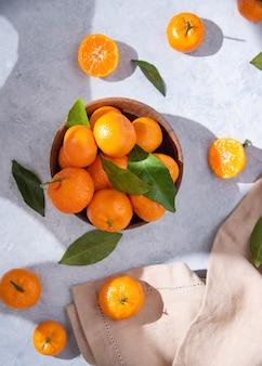 Mise à plat des mandarines sucrées et juteuses dans un bol en bois et quelques mandarines sur fond bleu avec les ombres du matin. vue de dessus