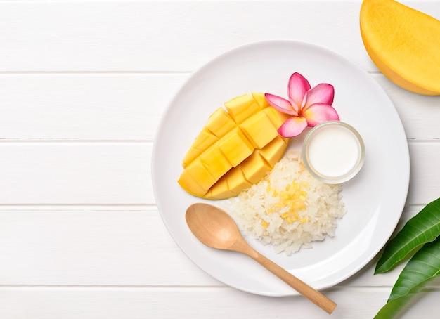 Mise à plat de mangue mûre avec riz gluant et lait de coco sur bois blanc