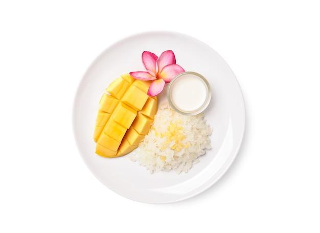 Mise à plat de mangue mûre avec riz gluant et lait de coco sur plaque blanche isolée sur blanc