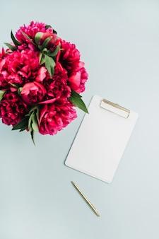 Mise à plat maquette avec presse-papiers et bouquet de fleurs de pivoine rose sur une surface bleu pastel