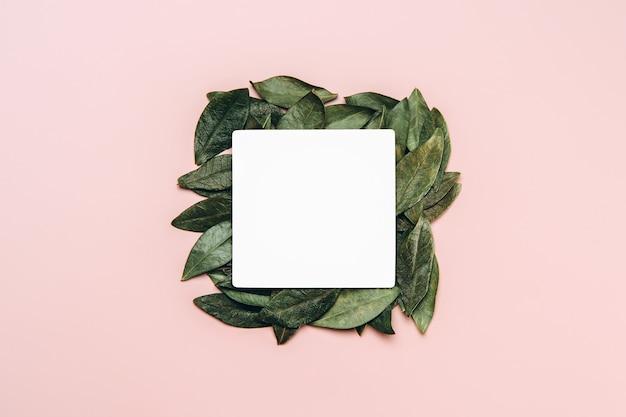 Mise à plat de maquette vierge blanche avec fond de feuilles naturelles vertes.