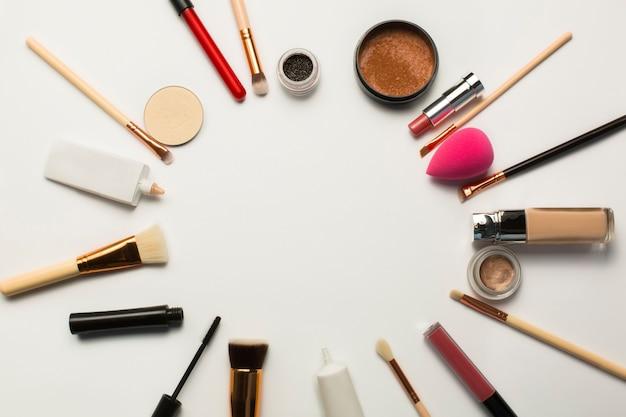 Mise à plat de mascara noir, pinceaux de maquillage et poudre bronzante sur fond blanc