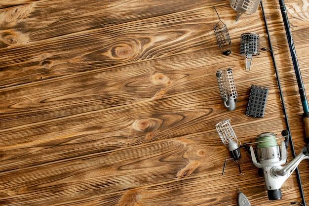 Mise à plat avec matériel de pêche, canne à pêche et boîte en plastique avec matériel de pêche et crochets, mangeoires sur des planches de bois, espace de copie.