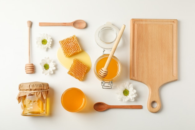 Mise à plat. miel, louche, cuillère et planche sur fond blanc