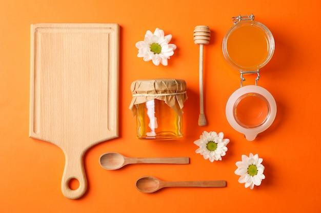 Mise à plat. miel, louche, cuillère et planche sur table