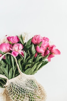 Mise à plat minimale, vue de dessus du bouquet de fleurs de pivoines blanches et roses isolé sur une surface blanche