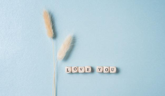 Mise à plat minimaliste avec des fleurs séchées blanches et des cubes avec les mots vous aiment