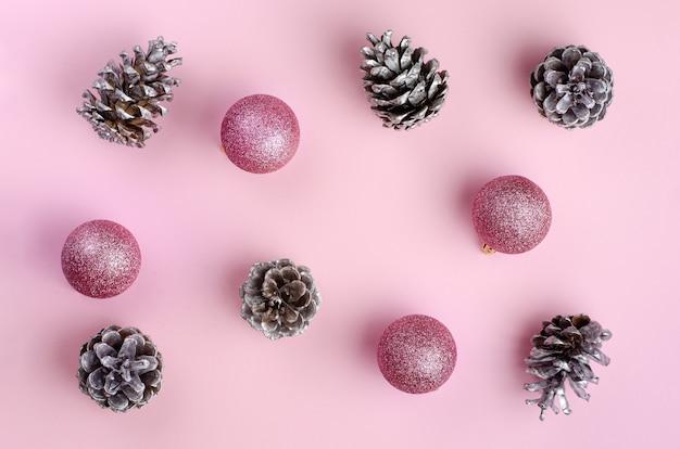 Mise à plat minimaliste de noël et du nouvel an avec des cônes d'argent et des boules de paillettes. rose festif