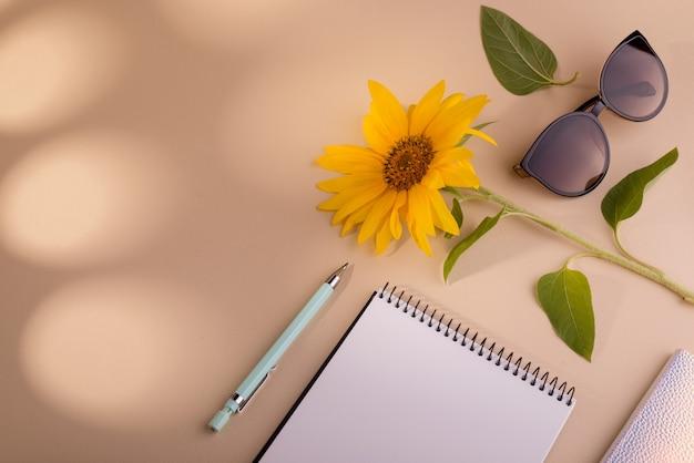 Mise à plat de mode avec des lunettes de soleil pour ordinateur portable tournesol et stylo sur fond beige