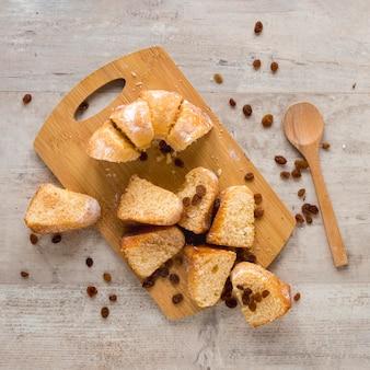 Mise à plat de morceaux de beignets sur une planche à découper avec des raisins secs
