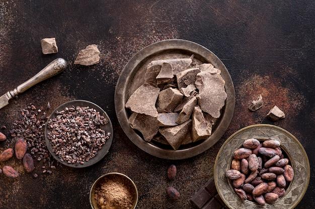 Mise à plat de morceaux de chocolat sur une plaque avec de la poudre de cacao et des haricots