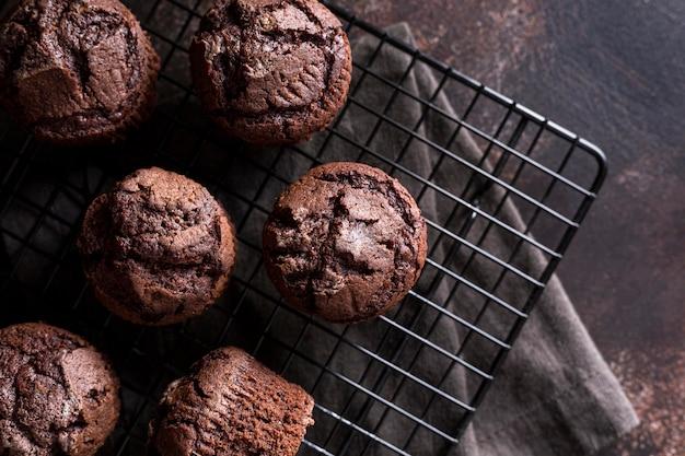 Mise à plat de muffins au chocolat sur une grille de refroidissement avec un chiffon