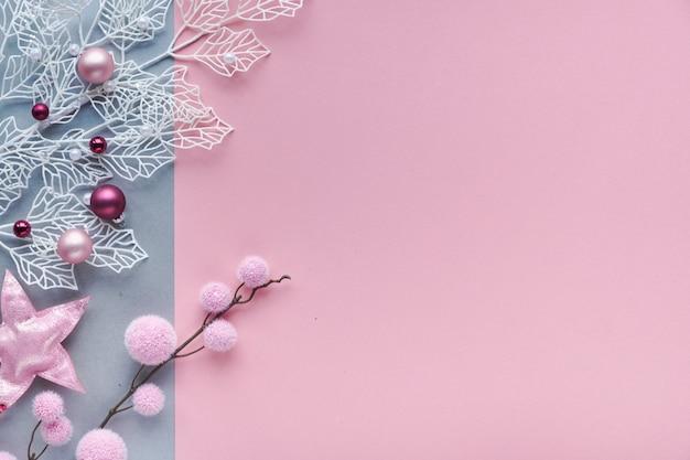 Mise à plat de noël romantique, vue de dessus sur fond de papier bicolore avec copie-espace. brindilles décoratives d'hiver blanches avec des feuilles géométriques givrées et des boules en textile doux et des bibelots en verre dispersés.