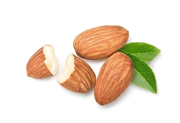 Mise à plat de noix d'amande avec coupe en deux et feuilles isolées sur fond blanc.