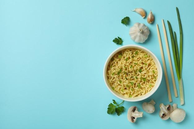 Mise à plat avec des nouilles et des ingrédients sur fond bleu