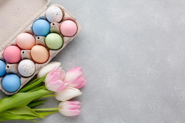 Mise à plat d'oeufs de pâques colorés dans un carton avec des tulipes et copie espace