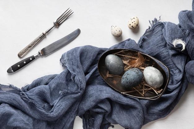 Mise à plat d'oeufs de pâques avec couverts et textile