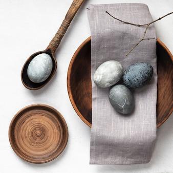 Mise à plat d'oeufs de pâques dans une cuillère en bois et plaque avec textile